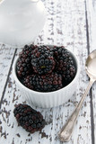 Blackberries in a bowl on a whitewashed table top