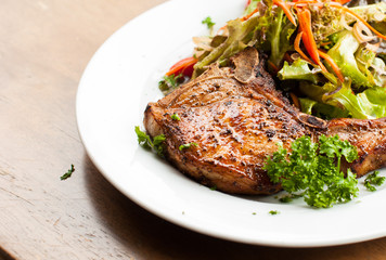 Pork chop with salad on table