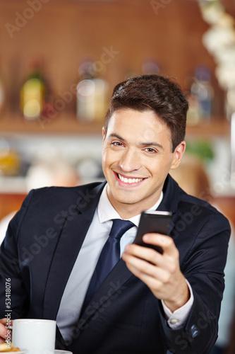 Geschäftsmann sitzt im Café mit Smartphone