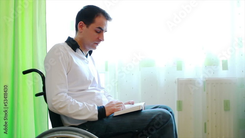 Young man in wheelchair reading a book