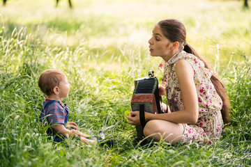 Young mother playing the accordion for young son