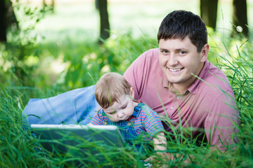 father with his son on nature with laptop