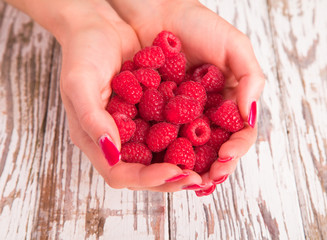 hands holding fresh berries on wood