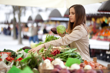 Young woman picking vegetables at farmer's market