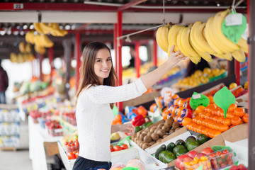 Young woman buying bananas at the market