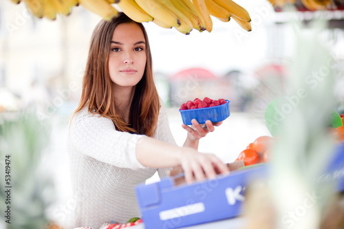 Young woman reaching for fruit at the farmer's market