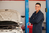 Young mechanic working at an auto shop and smiling