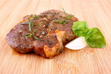 Juicy grilled steak on bamboo board with basil and onion