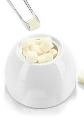 Refined sugar in white sugar bowl on grey background