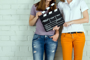 Two young girls holding a clapboard against brick wall with copy