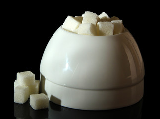 Refined sugar in white sugar bowl on black background