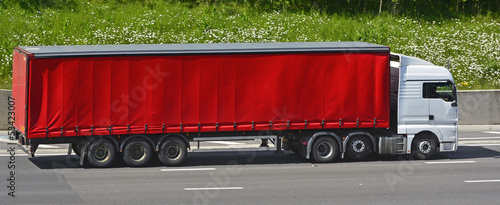 Red articulated soft sided trailer and white lorry