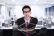 Angry businessman tied with rope at office
