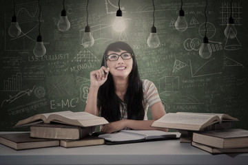 Asian student under light bulbs thinking in classroom