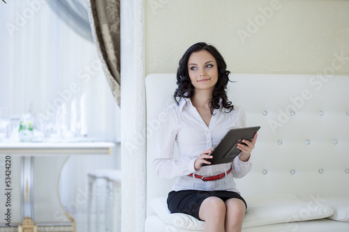 Charming girl posing with tablet PC in hotel room