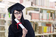 Beautiful woman in graduation gown pose at library
