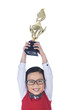 Boy holding trophy above his head - isolated