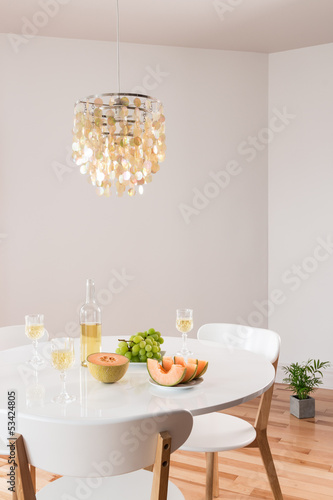 Decorative chandelier and elegant table with white wine