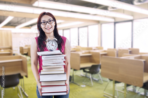 Happy female student bring stack of books and clock