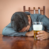 Drunk man sleeping on a table and holding a pint of beer