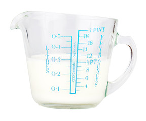 Measuring cup containing milk  isolated on white