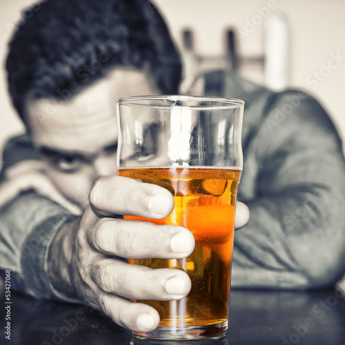 Grunge image of a drunk man holding a glass of beer
