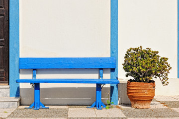 Blue wooden bench outside of chapel in Santorini Island