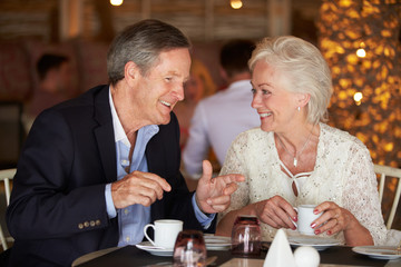 Senior Couple Enjoying Cup Of Coffee In Restaurant
