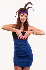beautiful young woman in a purple carnival mask, forming heart w
