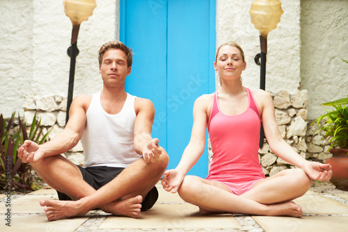 Couple Meditating Outdoors At Health Spa