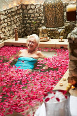 Senior Woman Relaxing In Flower Petal Covered Pool At Spa