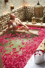Woman Relaxing In Flower Petal Covered Pool At Spa