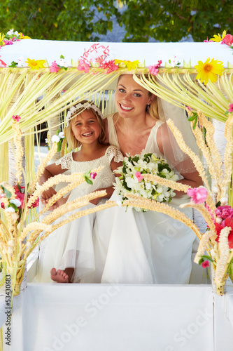 Bride And Bridesmaid Sitting Under Decorated Canopy