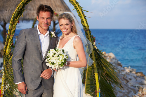 Bride And Groom Getting Married In Beach Ceremony