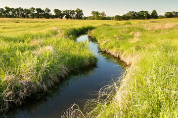 creek winding through Kansas pasture field