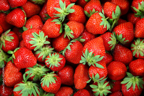Fresh strawberry fruit as a backdrop.