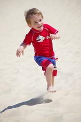 enfant blond courant sur la plage