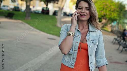 Pretty woman talking on cellphone in the city, steadicam shot