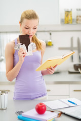 Teenage girl eating chocolate while studying in kitchen