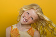 Beautiful blonde girl on a yellow background