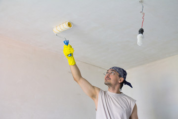 Young worker painting ceiling with roller