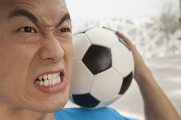 Close up of angry young man holding a soccer ball