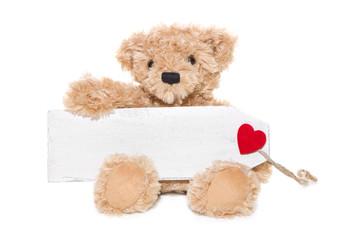 Teddybär mit Herz und Holzschild in der Hand isoliert
