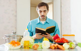 man reading cookbook for recipe