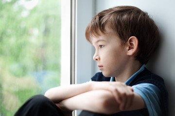 Sad boy sitting on window