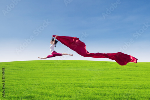 Beautiful female jumping with red scarf on field