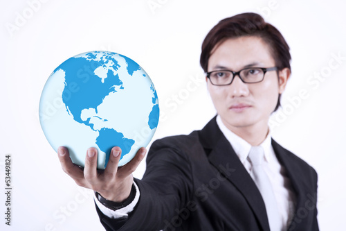 Businessman giving world globe on white