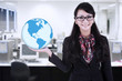 Businesswoman hold world globe at office