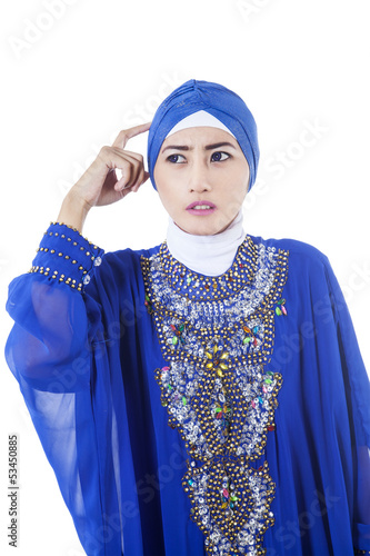 Confused female muslim in blue dress - isolated