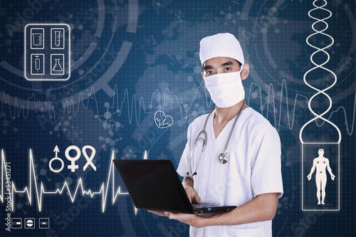 Doctor holding laptop on digital background